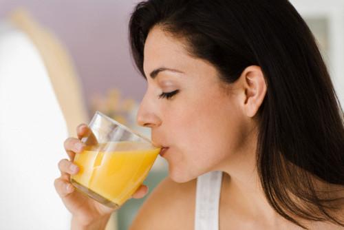 Woman Drinking Orange Juice --- Image by © Michael A. Keller/Corbis