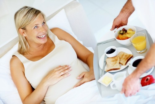 Portrait of a happy pregnant woman in bed being served a breakfast tray