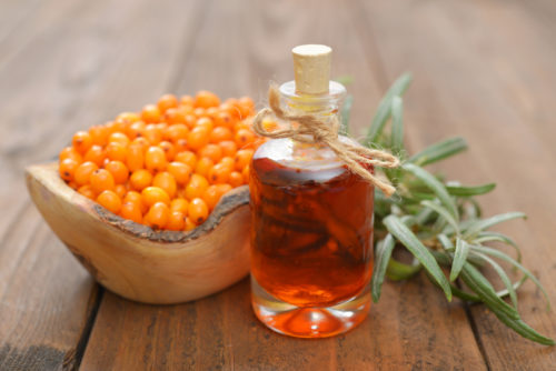 Sea-buckthorn oil and berries in bowl on a wooden background